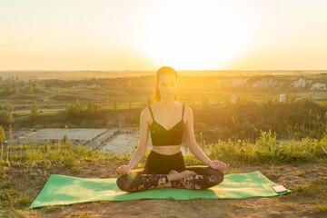 Young woman meditating in lotus pose on nature at sunset.