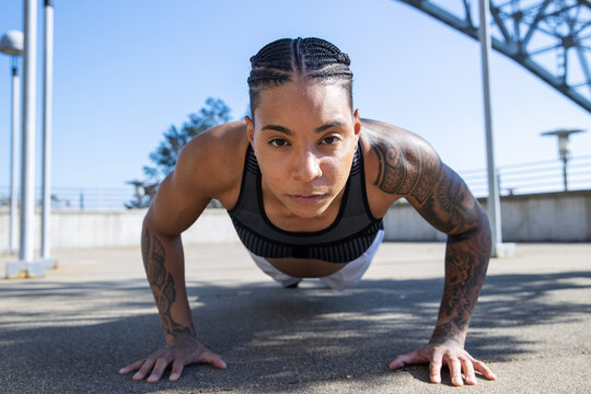 Strong black woman with tattoos doing pushups outside to build muscles