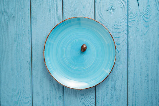 TOP VIEW: Last chocolate candy on a blue bowl on blue table