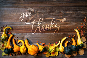 Colorful Yellow And Orange Pumpkins As Autumn Season Decoration With English Text Give Thanks. Brown Wooden Rustic Vintage Background