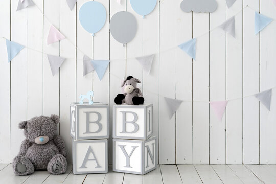 Word baby on wooden cubes near toys and decorated wall