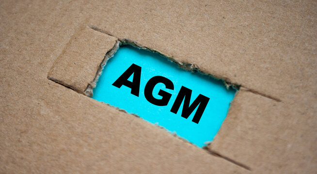 A cut-out hole in the paper cardboard, and under it a piece of paper with the word AGM. The word AGM
