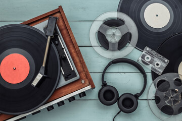 Fototapeta Retro vinyl record player with records, audio magnetic reel, audio cassette and stereo headphones on blue wooden background. Top view. Flat lay obraz