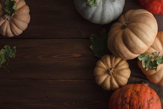 Thanksgiving background: Apples, pumpkins and fallen leaves on a wooden background. Copy space for text. Halloween, Thanksgiving, or seasonal fall. Design layout. Horizontal