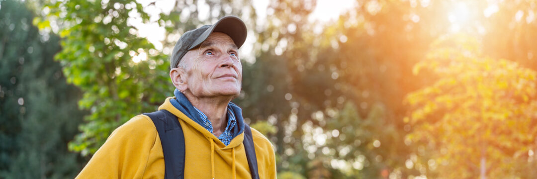 old happy male hiker with backpack looking on mountain top forest background