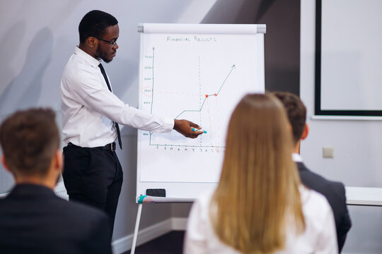 Serious African American mentor giving presentation explains sales growth graph by teaching different trainees in group meeting, new corporate plan on flipchart