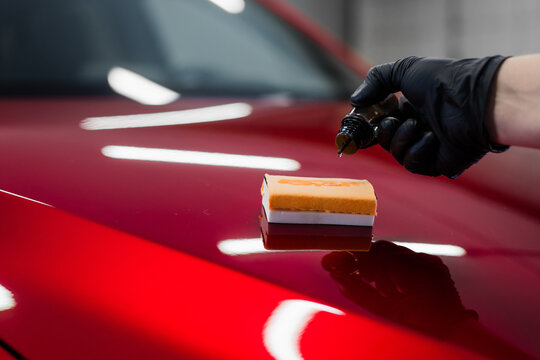 Car detailing - Man applies nano protective coating or wax on red car. Covering car bonnet with a liquid glass polish.