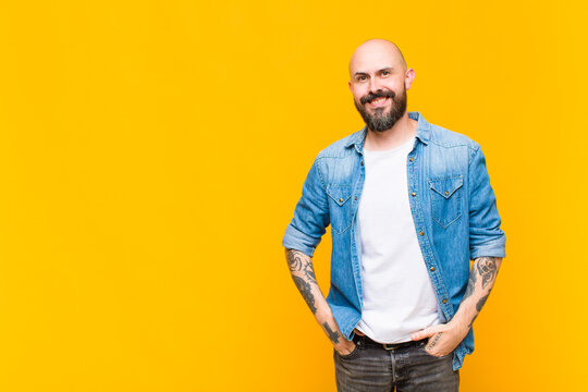 young bald and bearded man smiling cheerfully and casually with a positive, happy, confident and relaxed expression