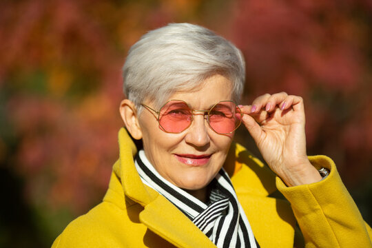 adult woman in pink sunglasses in the park in autumn