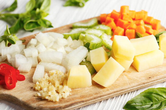 Fresh raw chopped vegetables for cooking soup on wooden board