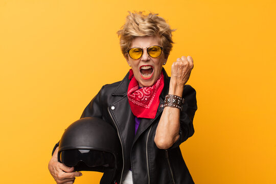 mature old beautiful woman shouting aggressively with an angry expression or with fists clenched celebrating success. motorbike concept