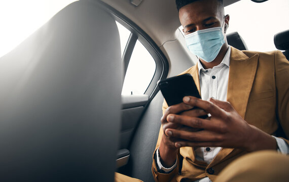 Young Businessman Wearing Mask Checking Mobile Phone In Back Of Taxi During Health Pandemic
