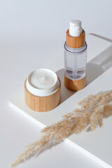 Set of natural organic cosmetics on white podium. Face moisturizer cream in eco friendly bamboo jar and lotion bottle with dried flowers. Skin care concept. Minimalist style.
