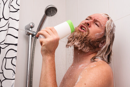 Handsome bearded man singing while taking shower at home using shampoo bottle instead of microphone. Happy caucasian guy sings with facial expression enjoying life.