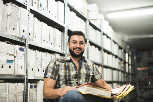 Man works in archive and reviews the different files