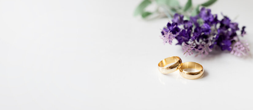 Purple flowers and two golden wedding rings on white background.