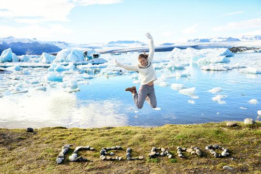 Iceland nature landscape Jokulsarlon glacial lagoon. ICELAND text written with rocks. Woman jumping having fun visiting tourist destination landmark attraction glacier lake, the famous Vatnajokull,