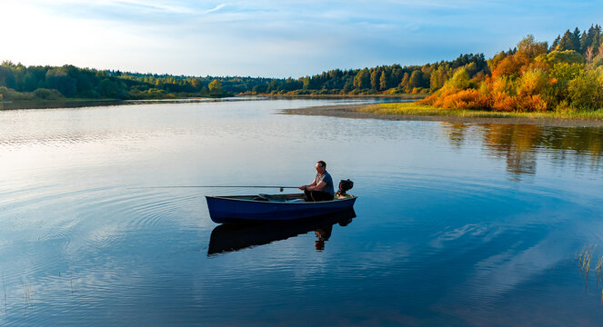 Elderly man fishing with a rod on a small fishing boat on the lake at autumn sunset