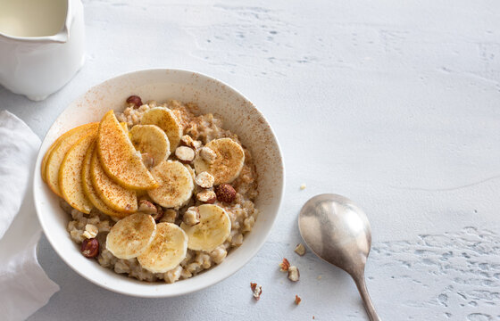 Delicious healthy breakfast. Oatmeal with banana, apple, nuts and cinnamon on a light gray background, top view, space