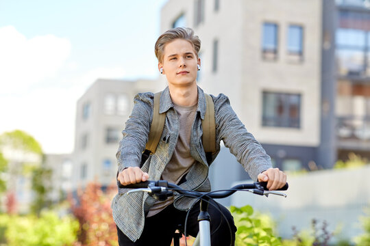 lifestyle, transport and people concept - young man or teenage student boy with backpack and earphones riding bicycle on city street