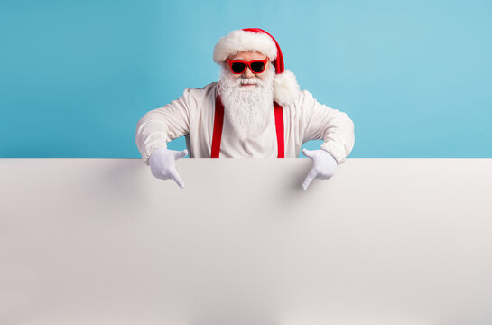 Portrait of his he nice attractive funky confident cool white-haired Santa demonstrating copy space board advice recommend look idea isolated over bright vivid shine vibrant blue color background