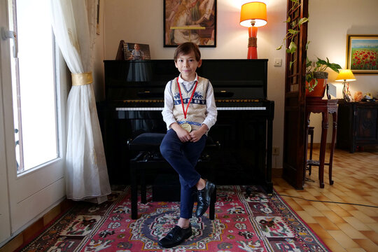 Guillaume Benoliel, a six-year-old child, poses with his medal of Grand Prize Virtuoso International Music in front of his piano at his home near Paris