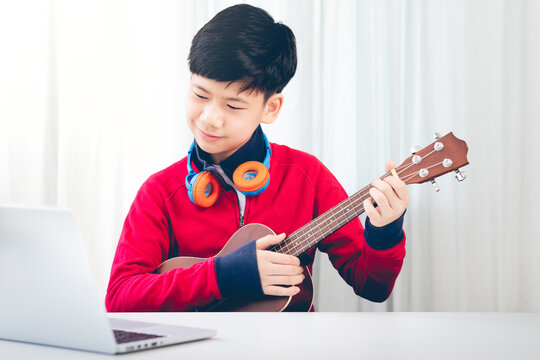 New normal, Online learning platforms - A good looking asian teenager boy remote learning music and his ukulele skills from online lesson during COVID-19 pandemic, Child's Educational, Healthy minds.