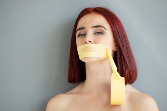 Young pretty woman with a mouth sealed with tape. Silence of social, gender and domestic violence concept. Girl who was silenced by people and circumstances