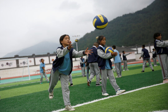 Students play volleyball during a P.E. class at the Wenchang Middle School in Yuexi
