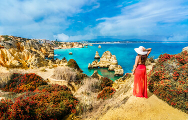Wall Mural - Landscape with unknown tourist girl is looking to the amazing view of spectacular rock formations, with caves, grottoes and sea arches in Lagos, Algarve, Portugal