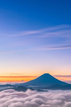 The peaks of Mount Fuji in summer rise above the clouds and the light of the sky during the sunrise