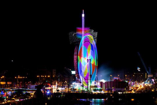 Riesenrad auf Volksfest / Rummel bei Nacht in Bewegung