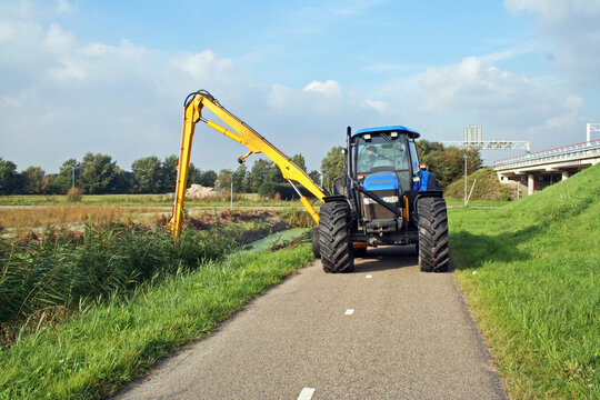 Summer ditch cleaning by a tractor in  a Dutch polder ;andscape