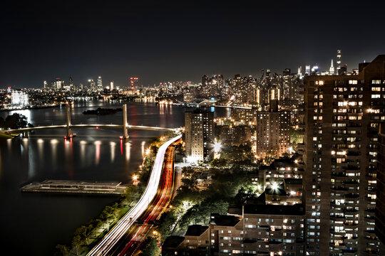 Blick von einem Wolkenkratzer in Harlem bei Nacht, in Richtung des Harlem Rivers. Große Skyline, eine Straße mit viel Verkehr, große rot-weiß gezeichnete Lichter von den Autos, einige Stadtlichter, La