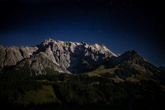 Ein Berg bei Nacht im Mondschein hell beleuchtet oberhalb Sterne und ein dunkelblauer kräftiger Himmel. Hochkönig Massiv im Salzburger Land.