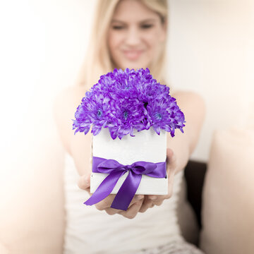 A young blonde is holding a bouquet of purple chrysanthemum flowers in a decorative box. The focus is on flowers.