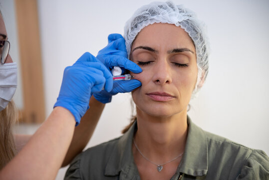 Beautiful, attractive, young woman, sitting relaxed in dermatologist ordination, getting a rejuvenating facial treatment with hyaluronic acid filler. Cosmetics and beauty  corrections and care concept