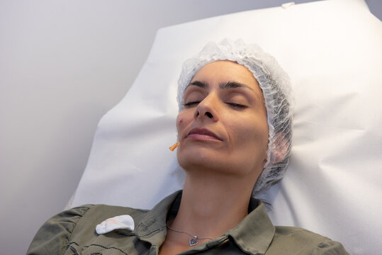 Beautiful attractive young woman lying in beauty salon with protective cap and needle in her cheek waiting for treatment