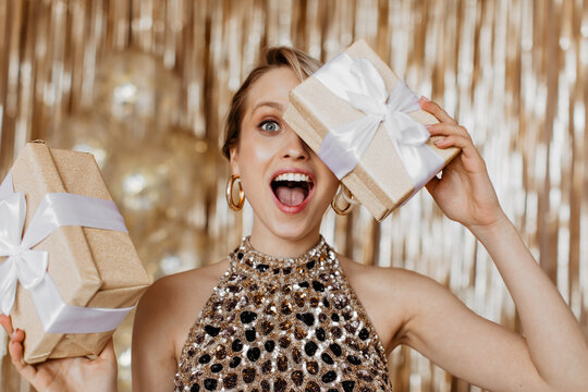 Emotional woman in elegant top covers her eyes with gift box with bow