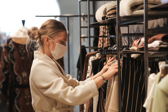 woman with mask chooses clothes inside a shop