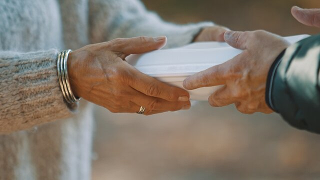 woman volunteer help feed the homeless with free meal. Close-Up. . High quality photo