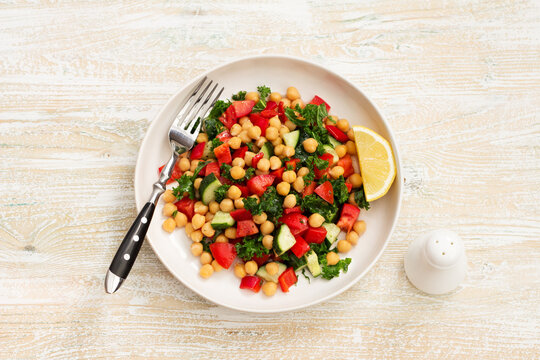 Healthy vegan salad with chickpeas, tomatoes, cucumbers, bell peppers and kale on light wooden background, flat lay
