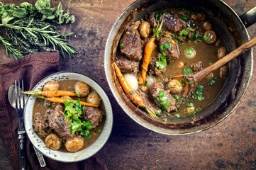 Traditional French boeuf bourguignon with vegetable farmhouse bread offered as top view in a design bowl