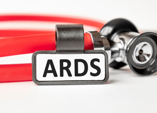 ARDS Acute respiratory distress syndrome. lettering on a business card with a holder, next to the red stethoscope. Medical concept. Treatment and prevention. Human health.