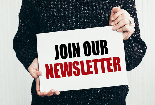 JOIN OUR NEWSLETTER text on notepad on women hands