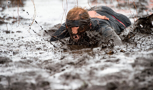 Mud race runners. Crawling,passing under a barbed wire obstacles during extreme obstacle race. Extreame sport concept