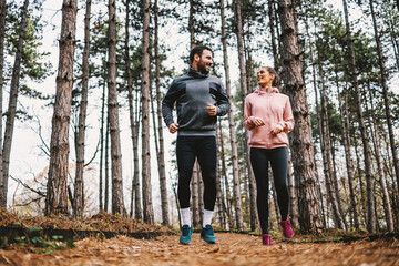 Full length of fit couple running trough woods at autumn and preparing for marathon.