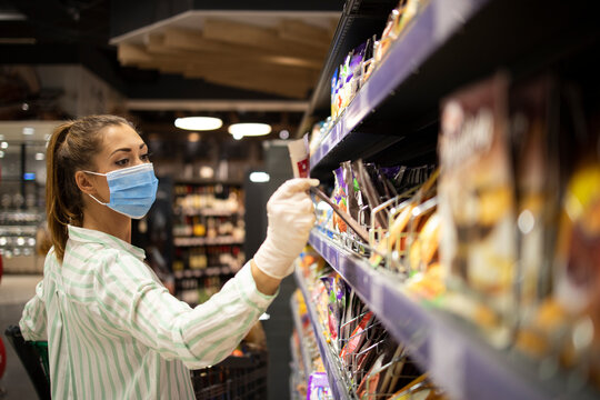 Woman protecting herself against corona virus or COVID-19 while shopping in supermarket. People wearing mask and gloves. Coronavirus safety measures.