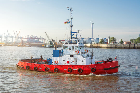 Red tugboat on the Elbe river in front of the harbour facilities in Hamburg, Germany
