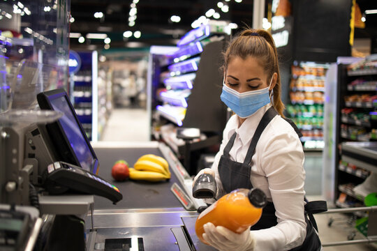 Cashier in supermarket wearing mask and gloves fully protected against corona virus. Working during covid-19 pandemic.